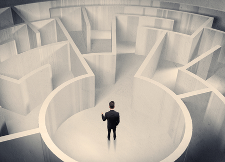 wayout: A confused businessman standing in the center of a maze surrounded with walls of the labyrinth