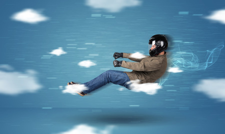 Funny racedriver young man driving between clouds concept on blue background photo