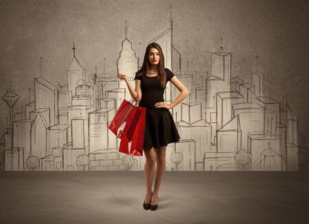 color model: An attractive young lady standing with red shopping bags in front of drawn city landscape silhouette concept Stock Photo