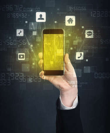 holographic: Caucasian hand in business suit holding a smartphone with golden-yellow holographic screen