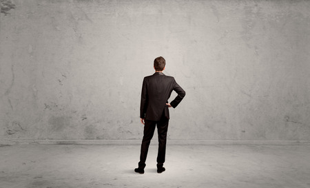 sales person: A confused sales person having a dilemma, standing with his back in empty grey urban environment concept Stock Photo