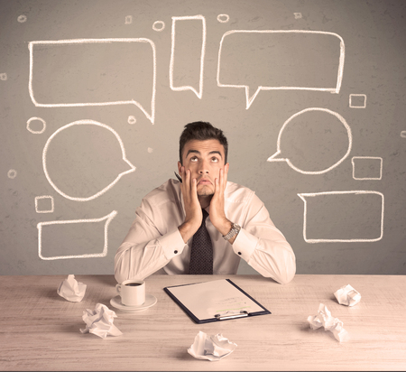 bad planning: An intelligent elegant business person sitting at a desk and working with drawn empty text bubbles, boxes around him concept Stock Photo