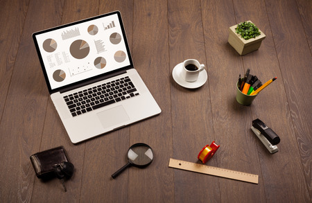 news values: Pie chart graph icons and symbols on laptop screen with office accessories Stock Photo