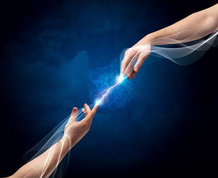 Dos brazos masculinos llegan a uno por el otro, con una corriente eléctrica fumar conexión de sus dedos en el vacío concepto de fondo del espacio