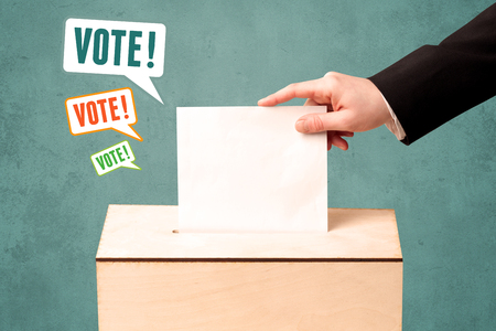 voting: A hand placing a voting slip into a ballot box Stock Photo