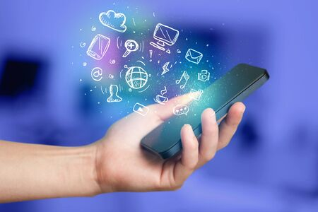 smartphone hand: Hand holding smartphone with glowing multimedia icons Stock Photo