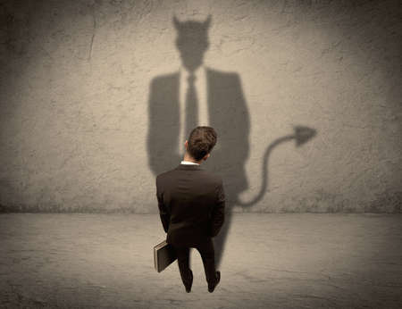 horn like: An experienced tricky businessman in suit looking at his devil desguise shadow reflected on the wall concept