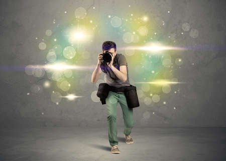 amateur: A young amateur photographer with professional camera equipment taking picture in front of grey wall full of colorful bokeh and glowing lights concept