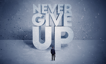 give out: A stressed out business worker standing in front of huge block letters saying never give up in blue open environment concept