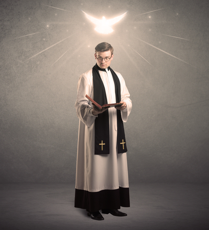 male angel: A holy priest reading a prayer from the holy bible with illustrated glowing angel above his head concept. Stock Photo