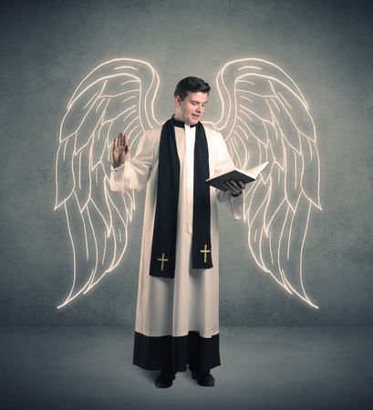 male angel: A young male priest with drawn large angel wings standing with the holy bible in his hands concept.