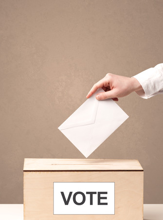 ballot papers: Close up of male hand putting vote into a ballot box, on grungy background