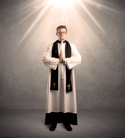 strong light: A male religious young priest in black and white dress giving his blessing, holding the holy bible while being illuminated from strong light beams coming from above concept