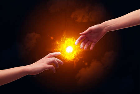 naked male: Two naked male hands about to touch, lighting a bright flame with smoke in red sky background concept