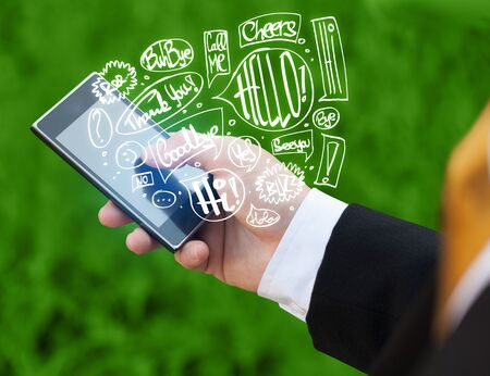 Hand holding phone with hand drawn speech bubbles concept Stock Photo