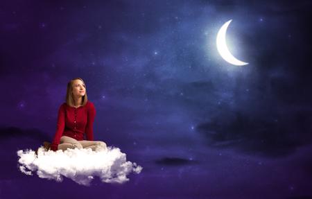 noche y luna: Mujer caucásica que se sienta y se pregunta en una nube blanca, bajo la luz de la luna Foto de archivo