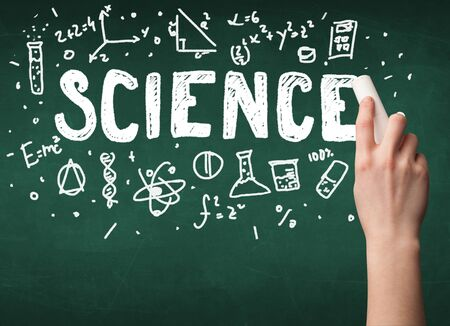 hand writing: A teacher writing science, drawing chemistry elements on clean green chalkboard by hand