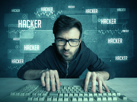 obsessive: A young handsome nerd hacking internet web sites while working on computer keyboard, with digital background illustration of numbers and letters concept