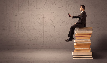 greyish: A serious businessman with tablet in hand in suit sitting on a pile of giant books in front of a greyish brown wall including drawn lines, angles, numbers, circles and curves.