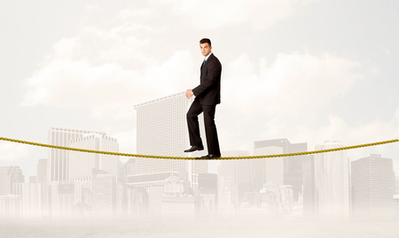 tight: A young elegant businessman walking on tight golden rope in front of city buildings landscape background concept Stock Photo