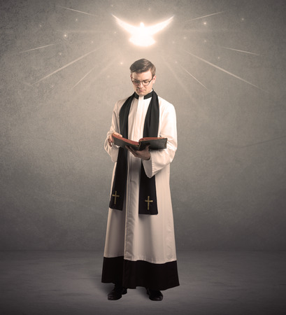 A holy priest reading a prayer from the holy bible with illustrated glowing angel above his head concept. Stock Photo