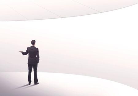 Jonge verkoop zakelijke persoon in elegante pak staat met zijn rug in lege witte ruimte achtergrond met gebogen lijnen-concept