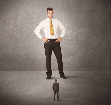 beat the competition: Big business man looking at small worker concept on background