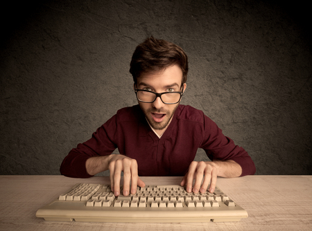 obsessive: A young hacker with glasses dressed in casual clothes sitting at a desk and working on a computer keyboard in front of black clear concrete wall background concept Stock Photo