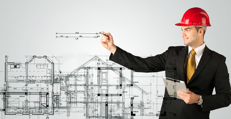 angles: A young architect planning and drawing a family house layout with measurements, lines, numbers, angles Stock Photo