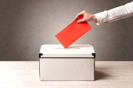 voting: Ballot box with person casting vote on blank voting slip, grungy background