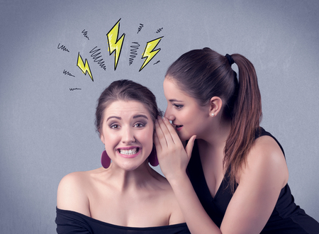 tattle: A beautiful girl in black dress sharing secrets to her girlfriend concept with drawn energetic electric yellow signs above her head on the wall background. Stock Photo