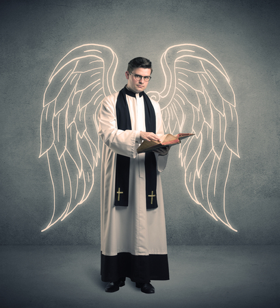 clergyman: A young male priest with drawn large angel wings standing with the holy bible in his hands concept.