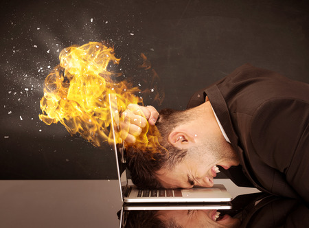 banging: A depressed businessman banging his head in a keyboard and shouting with his head on fire, reflecting on desk