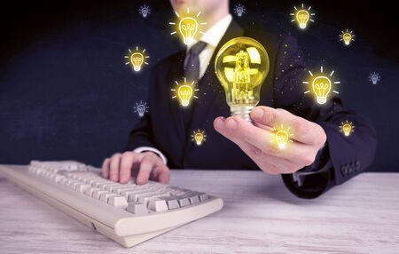Un hombre de negocios creativo tiene un concepto de idea brillante con la oficinista que sostiene la bombilla en primer plano.