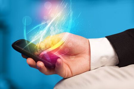 smart phone hand: Hand holding smart phone with abstract glowing lines concept