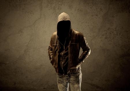 Un sospechoso de sexo masculino maduro sin rostro en el ambiente urbano oscuro y claro en frente de un fondo de hormigón pared vacía