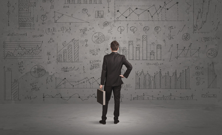 calculations: A successful confident businessman thinking about decisions, standing in front of wall full with graph pie charts and calculations concept