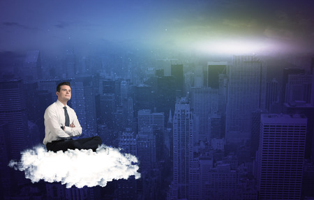 wondering: Caucasian businessman sitting on a white fluffy cloud above the city, thinking and wondering Stock Photo