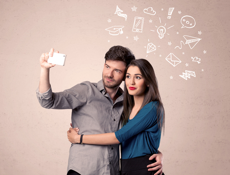 media love: A young couple in love taking selfie with a mobile phone in the handsome guys hand and drawn media communication icons above them, confused ideas concept Stock Photo