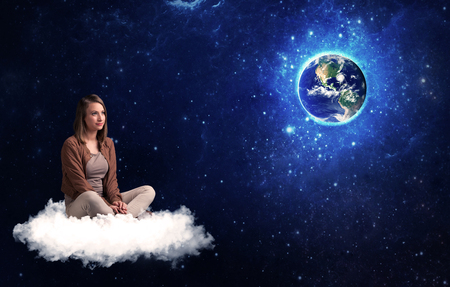 wondering: Caucasian woman sitting on a white fluffy cloud sitting and wondering at planet earth