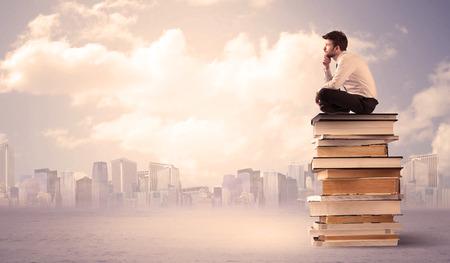 diligente: Un estudiante seus con la tableta portátil en traje elegante sentado en una pila de libros delante del paisaje urbano con las nubes Foto de archivo