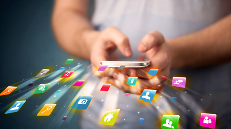 Man holding smartphone with technology application icons comming out Stock Photo