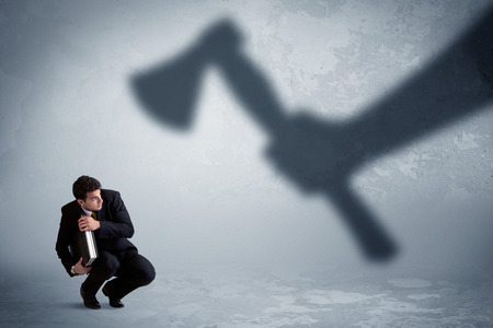 employe: Businessman afraid of a huge shadow hand holding an axe concept on background Stock Photo