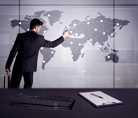 office environment: A young office worker drawing on world map and connecting dots with lines, presenting marketing sterategy at office environment concept