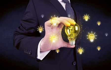 light worker: A creative businessman has a bright idea concept with office worker holding light bulb in foreground.