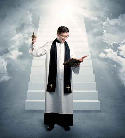 clergyman: A young religious happy priest standing in front of the stairway to heaven concept with clouds and bright lights coming from above. Stock Photo