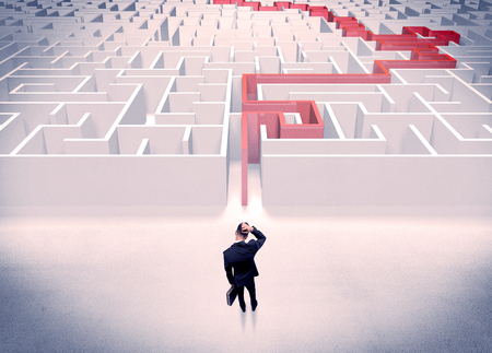 wayout: A businessman in suit giving thumbs up in front of labyrinth with red line showing the way out Stock Photo