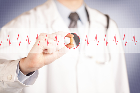 A male doctor in white coat with a stethoscope on one shoulder holding a pill between his fingers focused on a heartbeat graph Stock Photo