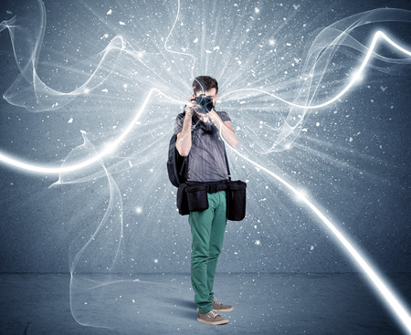 amateur: A young amateur photographer with professional photographic equipment taking picture in front of blue wall with dynamic white lines illustration concept Foto de archivo