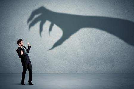 Business persona ha paura di un grande concetto di ombra mostro artiglio su sfondo Archivio Fotografico